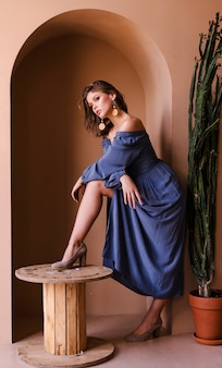 Jovem menina morena de vestido azul casual posando no quarto bege