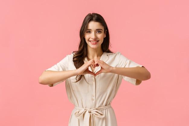 Jovem menina morena de vestido, mostrando sinal de coração