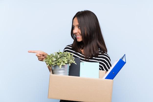 Jovem menina morena fazendo um movimento ao pegar uma caixa cheia de coisas apontando para o lado para apresentar um produto