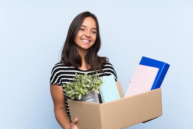 Jovem menina morena fazendo um movimento ao pegar uma caixa cheia de coisas com expressão feliz