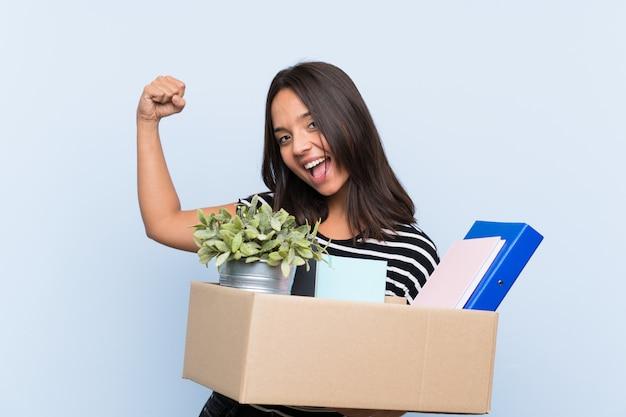 Jovem menina morena fazendo um movimento ao pegar uma caixa cheia de coisas comemorando uma vitória
