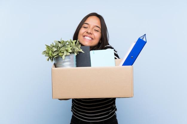 Jovem menina morena fazendo um movimento ao pegar uma caixa cheia de coisas