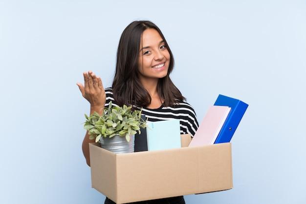 Jovem menina morena fazendo uma jogada ao pegar uma caixa cheia de coisas convidando para vir com a mão. feliz que você veio