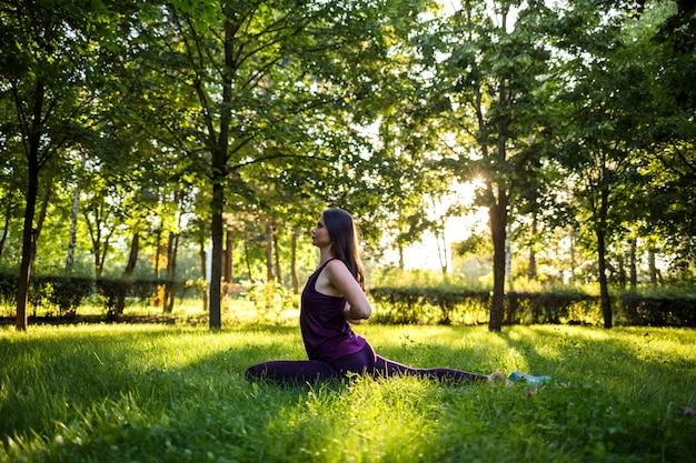 Jovem menina morena fazendo yoga em uma esteira no parque ao pôr do sol