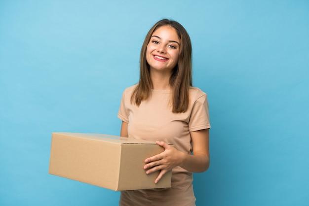 Jovem menina morena isolada segurando uma caixa para movê-lo para outro site