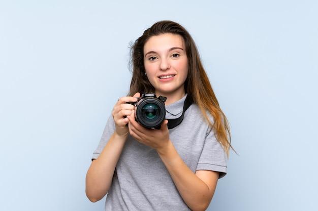 Jovem menina morena isolado parede azul com uma câmera profissional