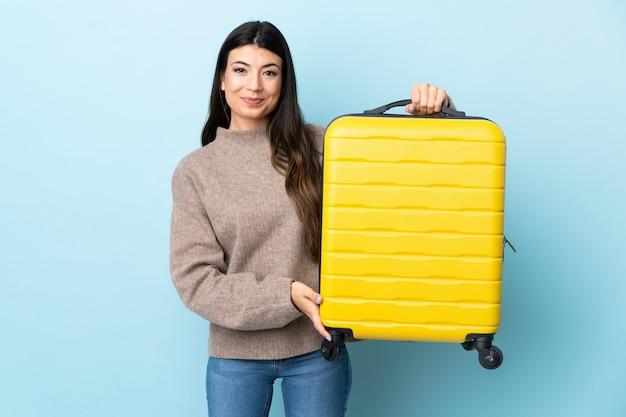 Jovem menina morena isolado parede azul em férias com mala de viagem
