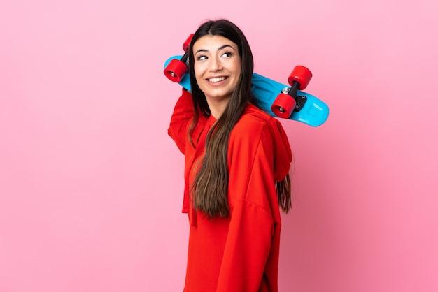 Jovem menina morena isolado rosa com um skate com expressão feliz