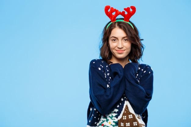 Jovem menina morena linda camisola de malha e chifres de rena de natal sorrindo sobre parede azul