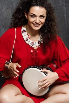 Jovem menina morena linda tocando tambor sobre parede cinza