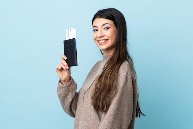 Jovem menina morena parede azul feliz em férias com bilhetes de avião e passaporte