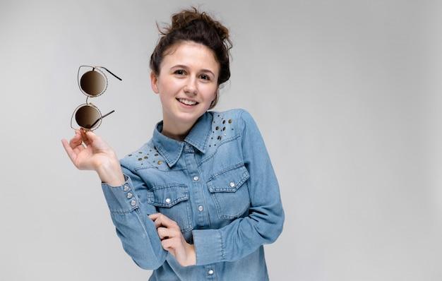 Jovem menina morena segurando óculos na mão. óculos de gato. o cabelo está reunido em um coque.