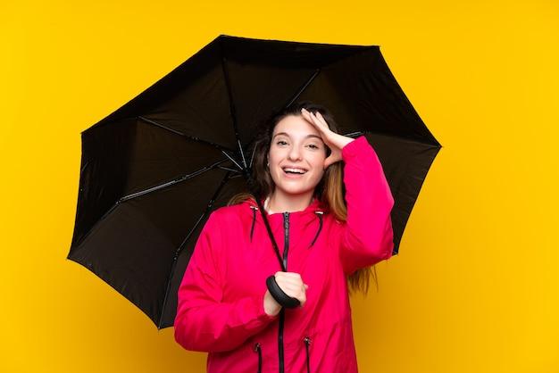 Jovem menina morena segurando um guarda-chuva sobre parede amarela isolada com surpresa e expressão facial chocada