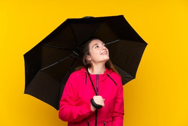 Jovem menina morena segurando um guarda-chuva sobre parede amarela isolada, olhando para cima enquanto sorrindo