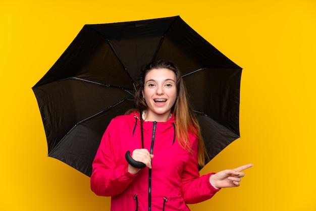 Jovem menina morena segurando um guarda-chuva sobre parede amarela isolada surpreendeu e apontando o dedo para o lado