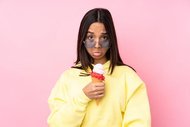 Jovem menina morena segurando um sorvete de corneta sobre rosa com expressão triste e deprimida