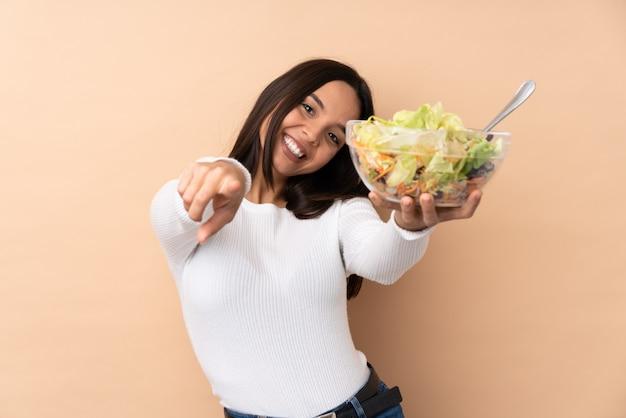 Jovem menina morena segurando uma salada sobre parede isolada aponta o dedo para você enquanto sorrindo