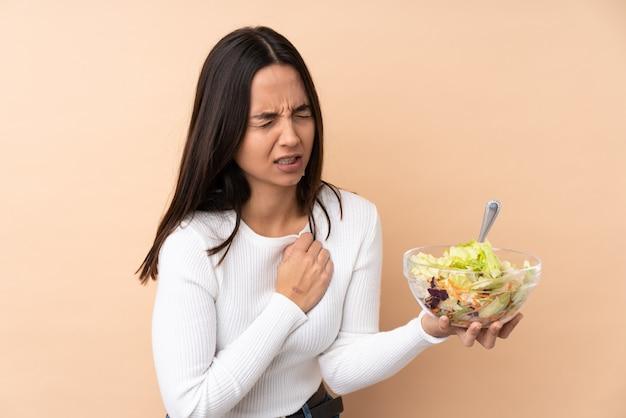 Jovem menina morena segurando uma salada sobre parede isolada, com uma dor no coração