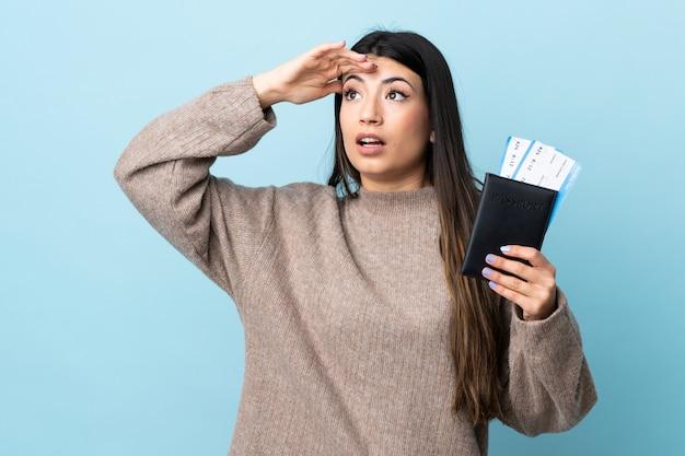 Jovem menina morena sobre parede azul em férias com bilhetes de passaporte e avião enquanto procura algo à distância