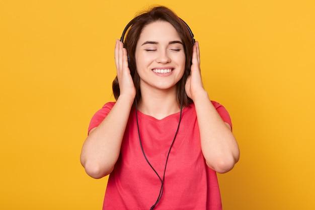Jovem menina morena sorridente com os olhos fechados, vestindo camiseta vermelha, ouvindo música através de fones de ouvido