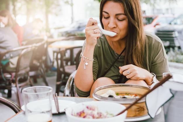 Jovem menina morena sorridente comendo dim sum no café rua asiática