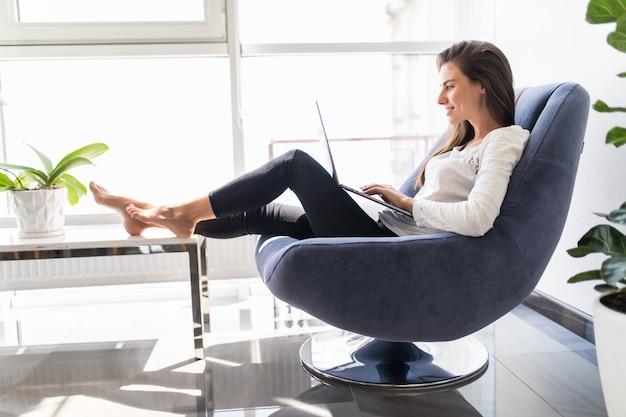 Jovem menina morena sorridente está sentado na cadeira moderna perto da janela na sala de luz acolhedora em casa trabalhando no laptop em ambiente relaxante