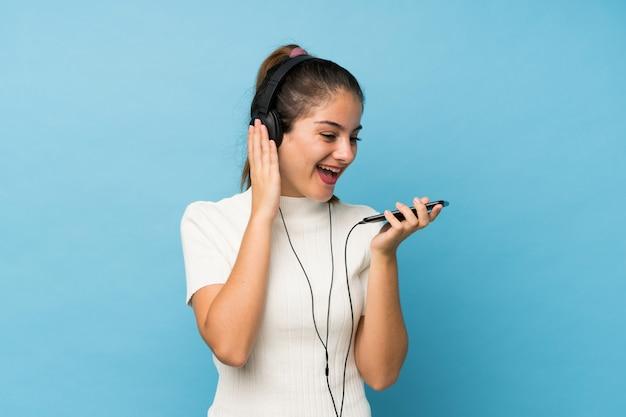 Jovem menina morena usando o celular com fones de ouvido e cantando