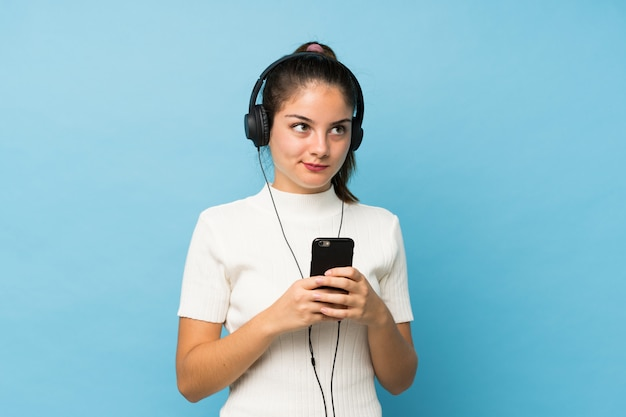 Jovem menina morena usando o celular com fones de ouvido e pensando