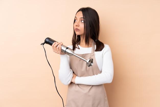 Jovem menina morena usando o liquidificador de mão sobre retrato de parede isolado