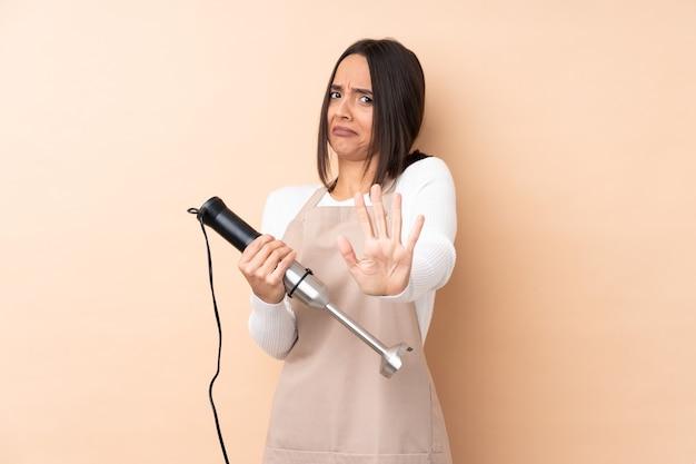 Jovem menina morena usando um liquidificador de mão sobre uma parede isolada nervosa, esticando as mãos para a frente