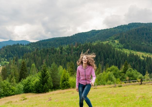 Jovem menina rindo na montanha do pico com vista perfeita.