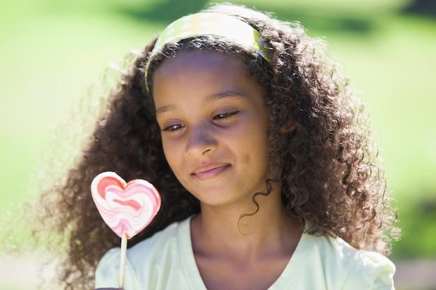 Jovem, menina, segurando, coração, lollipop, parque