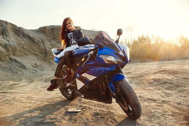 Jovem menina sentada em uma motocicleta, linda motociclista em uma bicicleta esportiva na natureza. a filha de um piloto de moto. rússia, sverdlovsk, 24 de setembro de 2018
