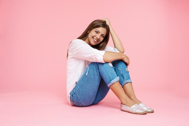 Jovem menina sorridente, sentada no chão, abraçando os joelhos, olhando em linha reta