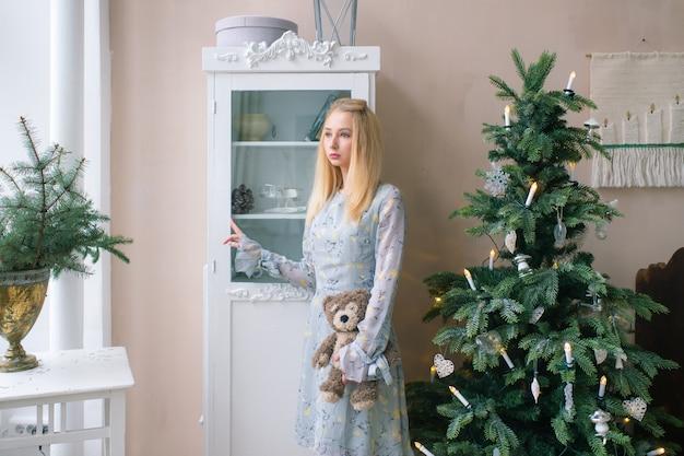 Jovem menina triste segurando crianças brinquedo na sala interior de natal com enfeites