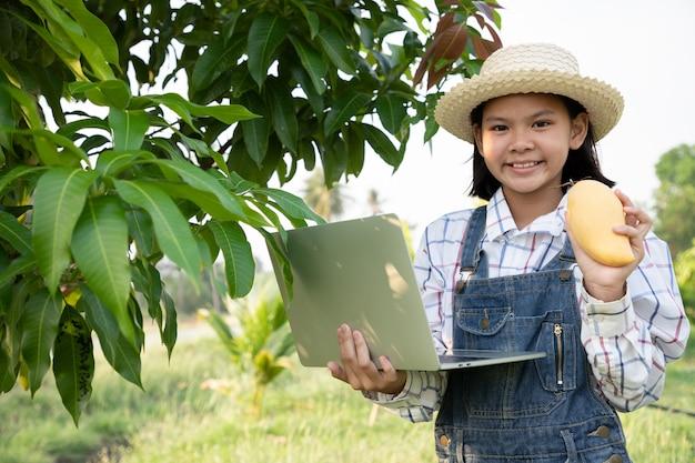 Jovem menina verificar e manter os produtos da fazenda de manga e usando um laptop computadorizado para verificar a qualidade. o agricultor é uma profissão que requer paciência e diligência. ser agricultor.