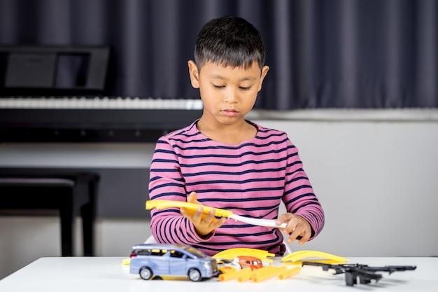 Jovem, menino asiático, jogando carro, brinquedo, em, a, sala