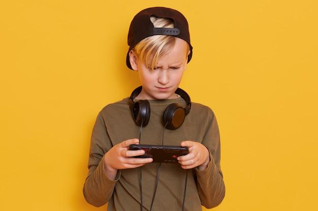 Jovem menino caucasiano usando telefone celular contra amarelo, cara parece concentrado, segurando seu telefone móvel