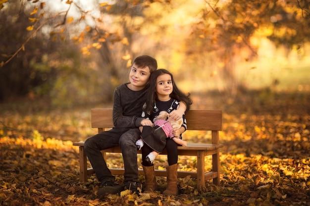 Jovem menino e menina sentada num banco de madeira no parque segurando uma boneca. tempo de outono. copie o espaço.