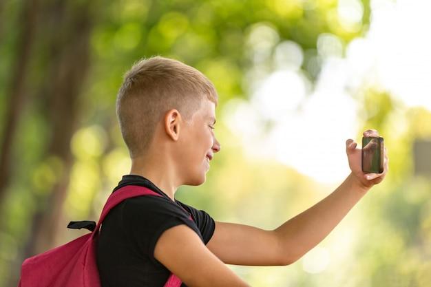 Jovem menino pré-adolescente feliz andando num dia quente de verão ensolarado no parque e tomando selfie no smartphone