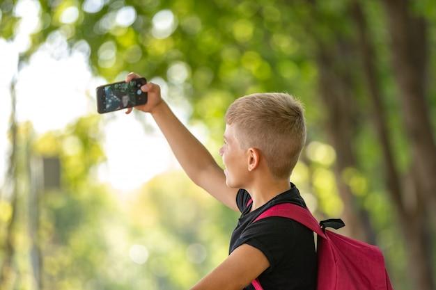 Jovem menino pré-adolescente feliz andando num dia quente de verão ensolarado no parque e tomando selfie no smartpone