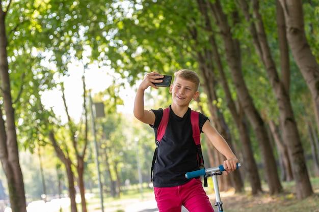 Jovem menino pré-adolescente feliz, montando uma scooter em dia quente de verão ensolarado no parque e tomando selfie no smartpone enquanto andava na scooter