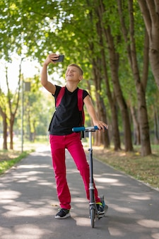 Jovem menino pré-adolescente feliz, montando uma scooter em um dia quente de verão ensolarado no parque e tomando selfie no smartpone