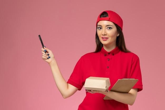 Jovem mensageira com capa de uniforme vermelha e um pequeno pacote de comida para entrega e um bloco de notas com uma caneta nas mãos na parede rosa claro.