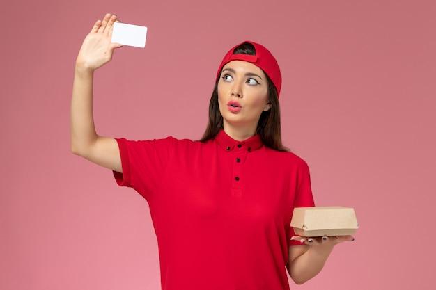 Jovem mensageira com capa de uniforme vermelha e um pequeno pacote de entrega de comida e cartão nas mãos na parede rosa