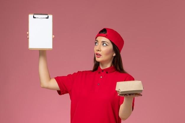 Jovem mensageira com capa de uniforme vermelha e um pequeno pacote de entrega de comida e um bloco de notas nas mãos na parede rosa