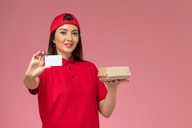 Jovem mensageira com capa de uniforme vermelho e um pequeno pacote de entrega de comida e um cartão nas mãos.