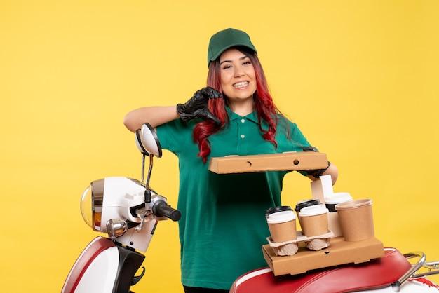 Jovem mensageira com entrega de café e comida em amarelo
