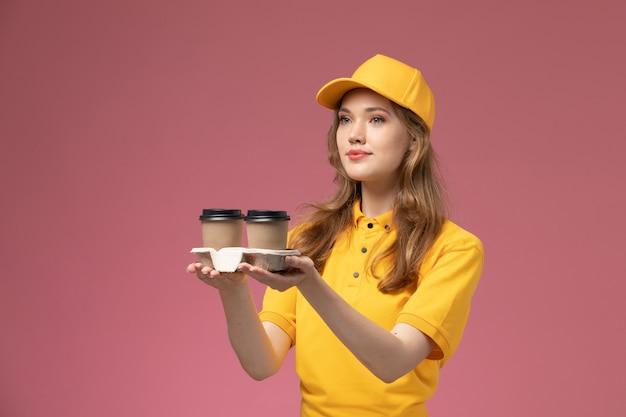 Jovem mensageira com uniforme amarelo, entregando café na mesa rosa, entregando uniforme de trabalho.