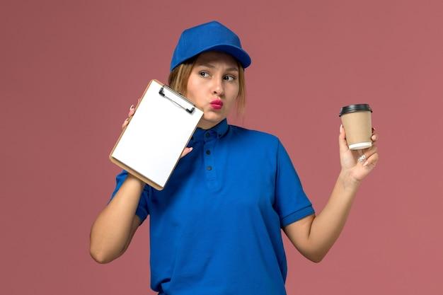 Jovem mensageira com uniforme azul, vista frontal, segurando a xícara de café e o bloco de notas, entregador de uniforme